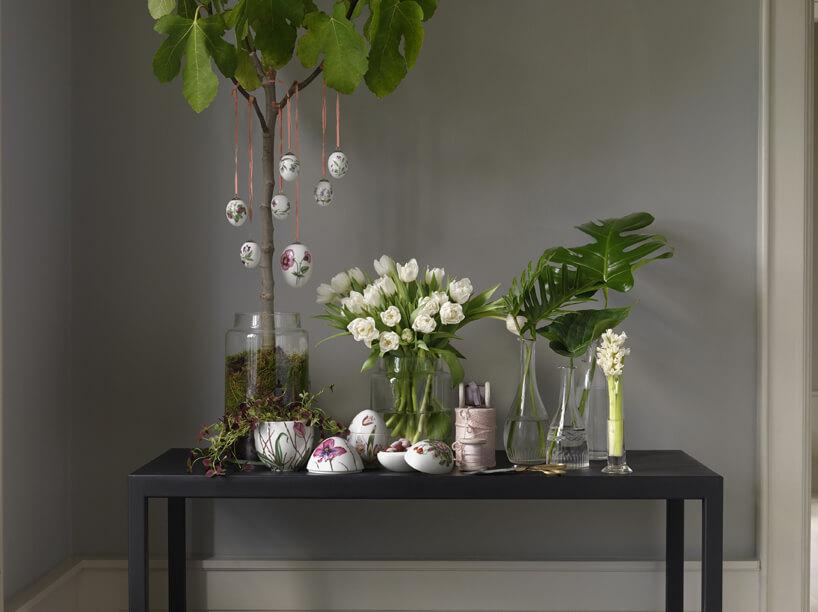 aranżacja ozdób wkształcie jajek ze wzorami kwiatowymi na tle szarej ściany