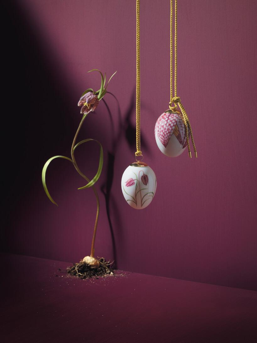 dwa jajka zwzorem kwiatów podwieszone na wstążkach na tle bordowej ściany