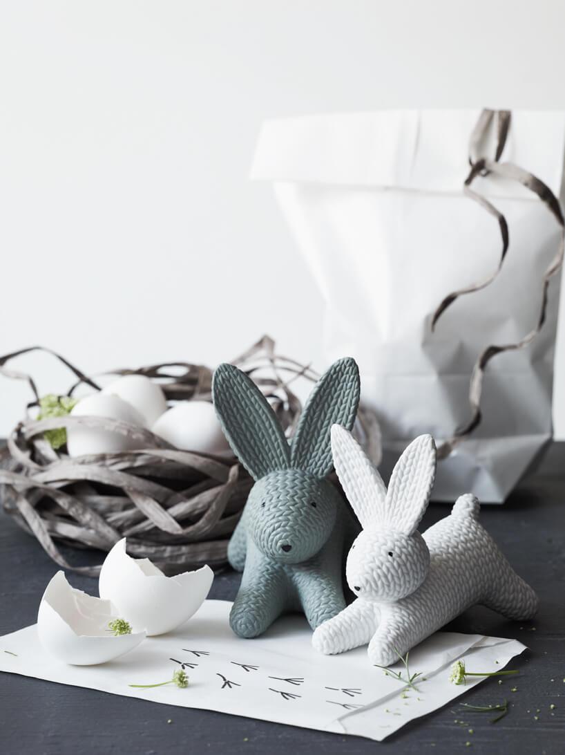 dwie figurki królików na ciemnym stole na tle koszyczka zjajkami