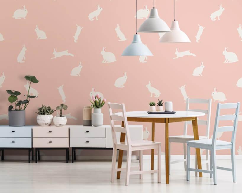 niska długa biała szafka obok stołu zkrzesłami na tle różowej tapety zbiałymi królikami