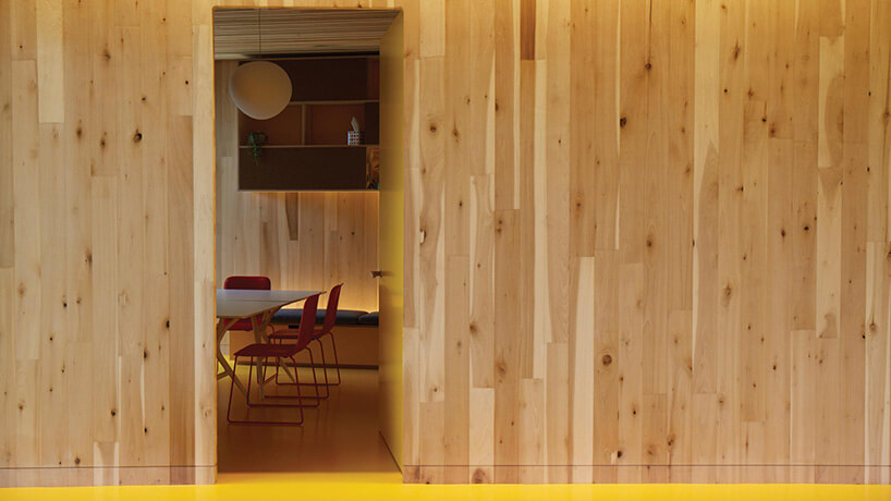 drewniana ściana ikawałek stołu ikrzeseł wpokoju