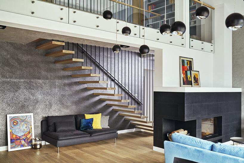 nowoczesne wnętrze domku jednorodzinnego zdrewnianym schodami na tle szarej ściany