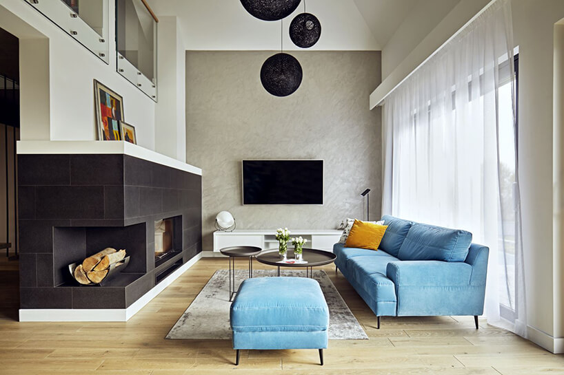 nowoczesne wnętrze salonu znarożnym ciemnym kominkiem iniebieską sofą