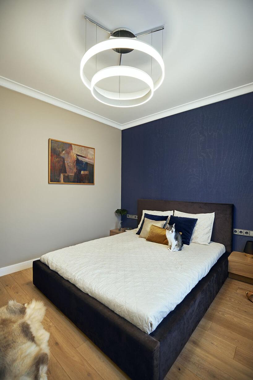 wyjątkowa sypialnia zczarnym łózkiem na tle niebieskiej fakturowanej ściany iwyjątkowym panelowym żyrandolu