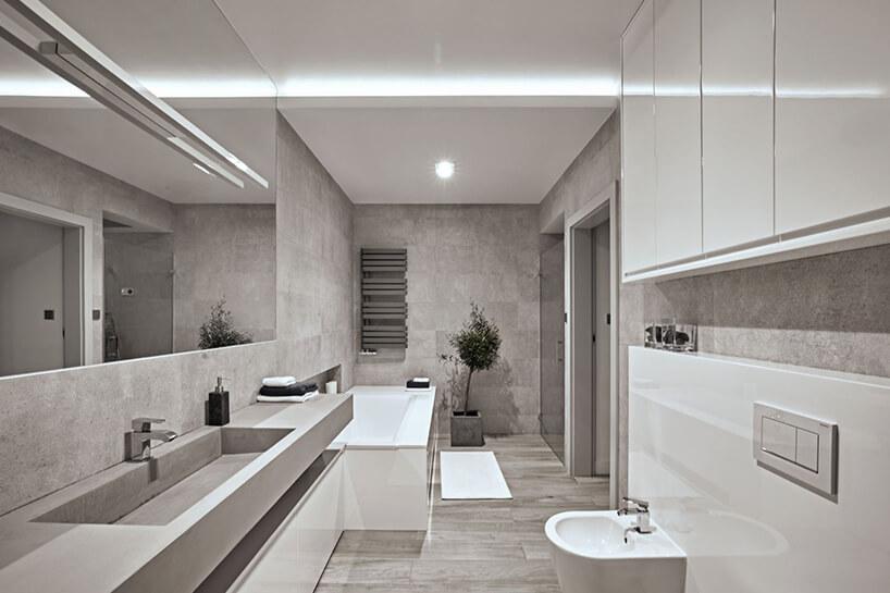 piękna inowoczesna duża łazienka wszarych płytkach ibiałymi błyszczącymi szafkami