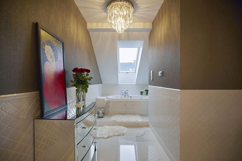 elegancka łazienka na poddaszu zdużą wanną pod wyjątkowym dużym żyrandolu