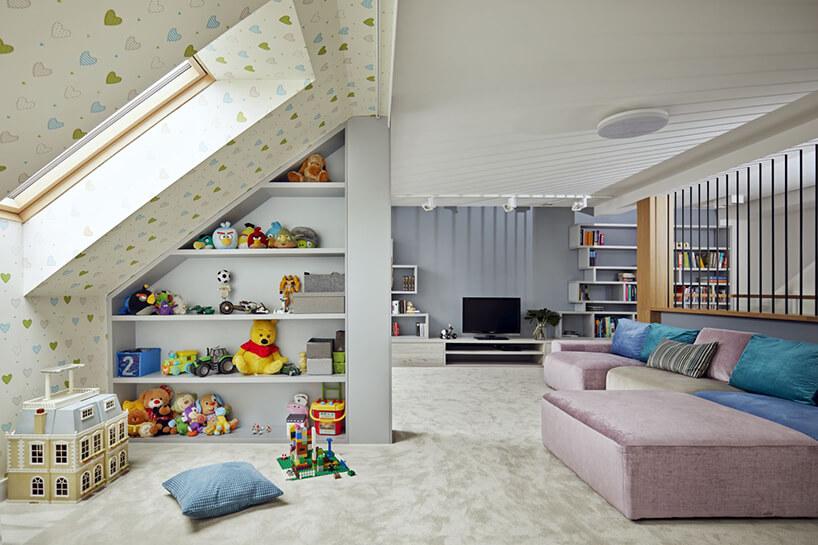 nowoczesne poddasze zprzestrzenią dla dzieci obok dużej kolorowej sofy