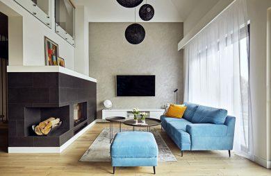 nowoczesne wnętrze salonu z narożnym ciemnym kominkiem i niebieską sofą