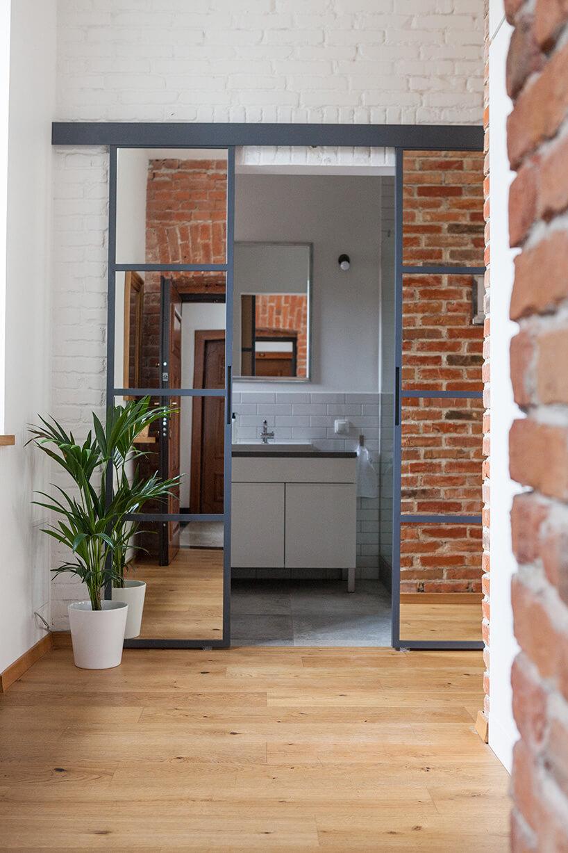 nowoczesny dom zcegłą na ścianie oraz metalowymi drzwiami