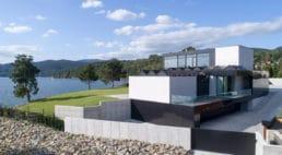 betonowe ogrodzenie wraz zmetalowymi szarymi poprzeczkami wnowoczesnym domu
