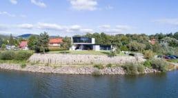 biały dom zczarnymi akcentami przy domu zczerwoną dachówką