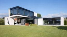 dom na wzgórzu wstylu nowoczesnym zpłaskim dachem oraz czarnymi dodatkami