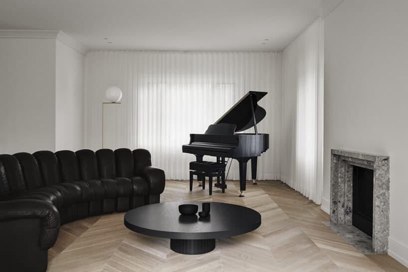 salon zminimalistycznym wystrojem oraz czarnym fortepianem wpołysku zasłonach