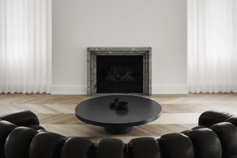 zaokrąglona duża kanapa naprzeciwko minimalistycznego kominka wsalonie