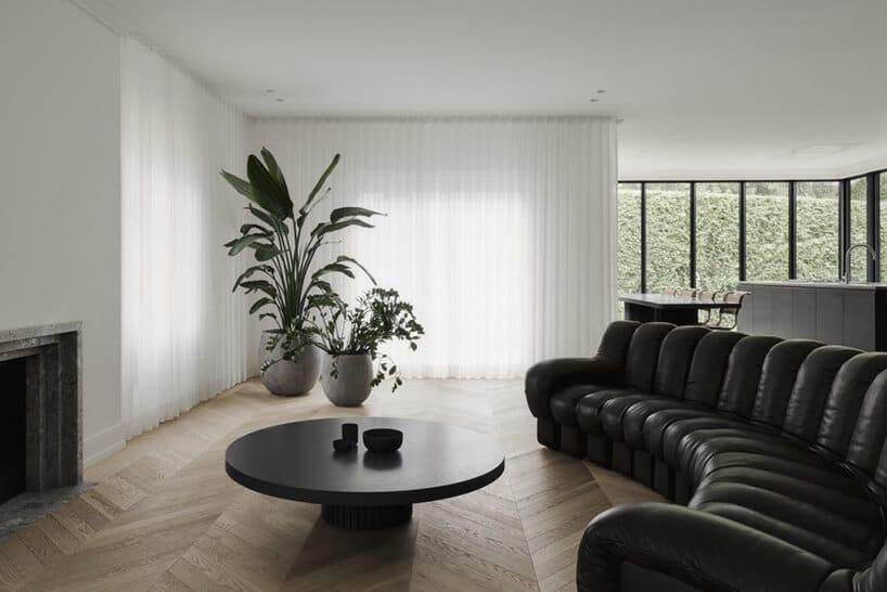 salon zczarnym okrągłym stolikiem oraz półokrągłą kanapa skórzaną