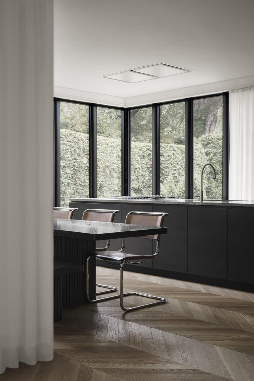 minimalistyczne wnętrze wkolorze czarnego matu oraz chromowanych elementów krzeseł