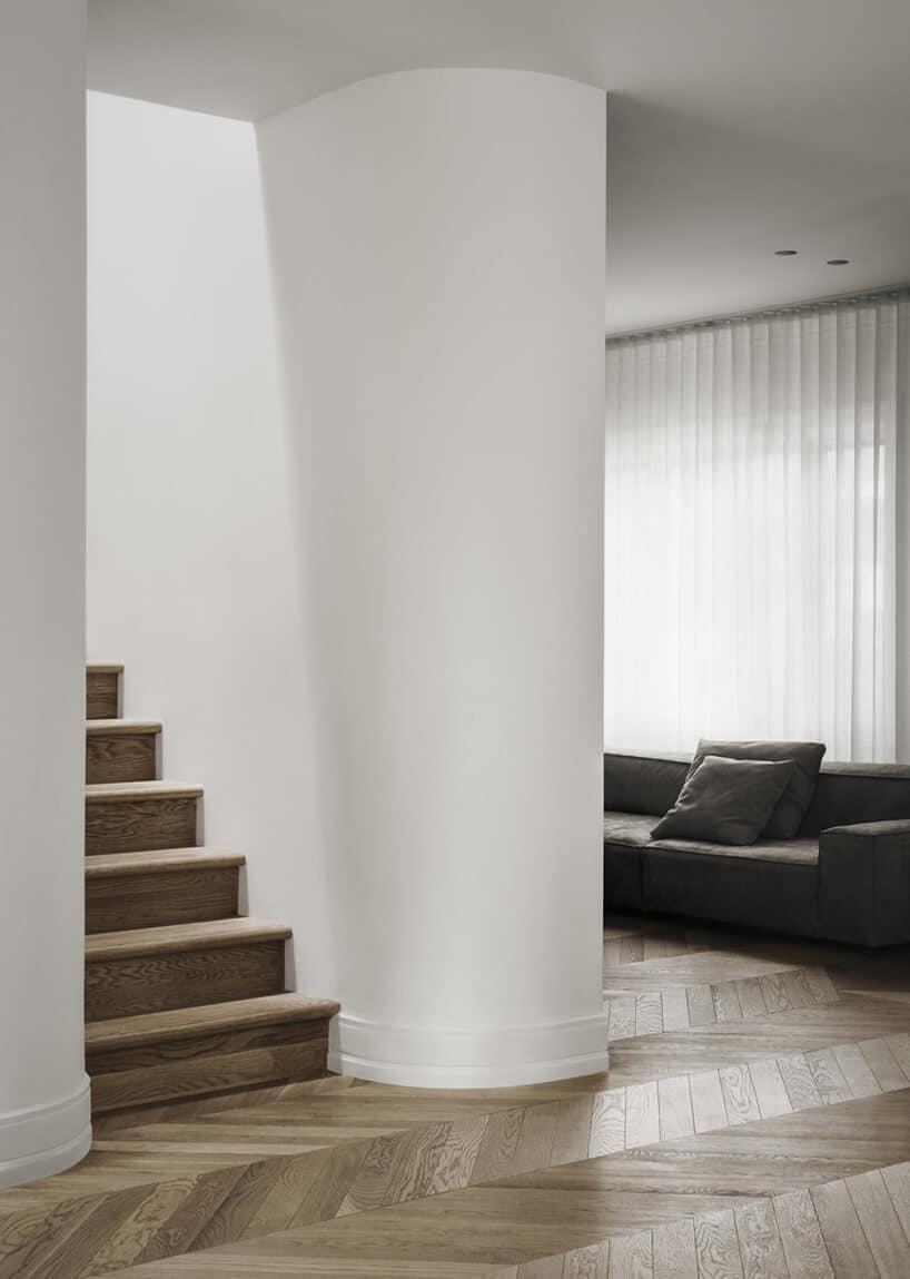 drewniane stopnie pomiędzy białymi ścianami oraz zaokrągleniem ściany
