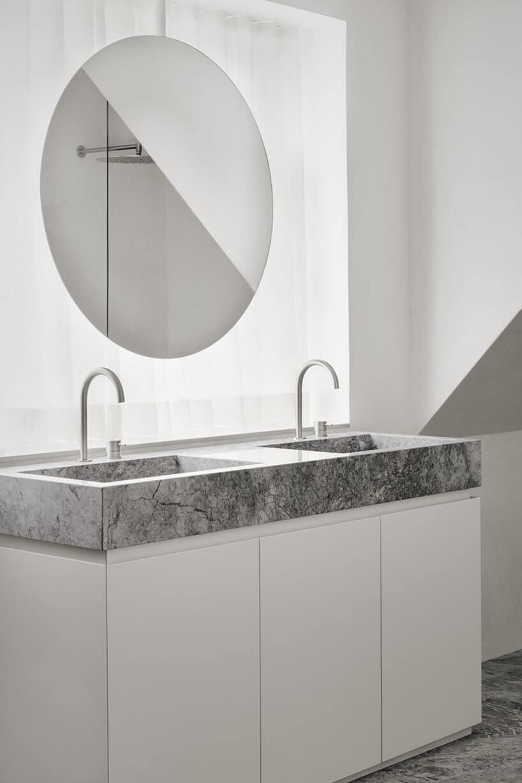 łazienka zdużym okrągłym lustrem oraz umywalkami wblacie zmarmuru