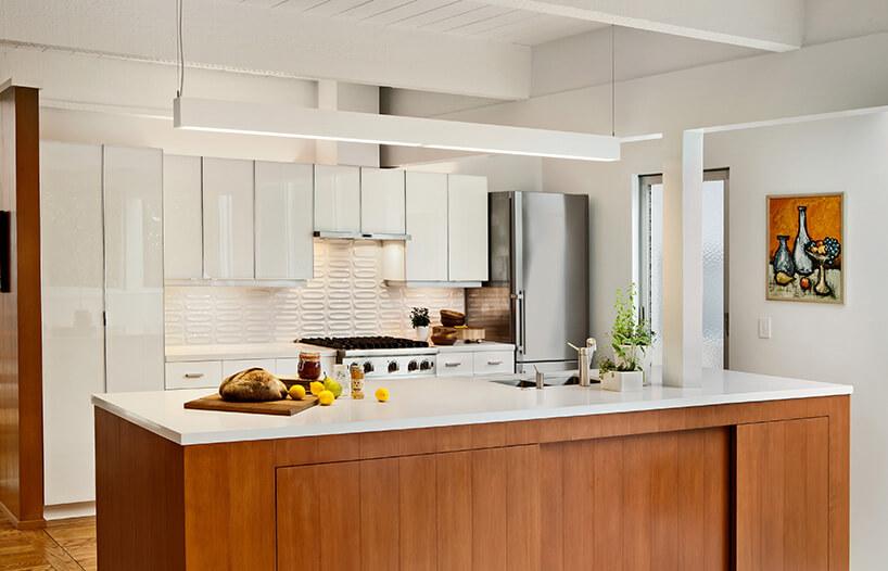 biała kuchnia iwyspa oddzielająca ją od salonu