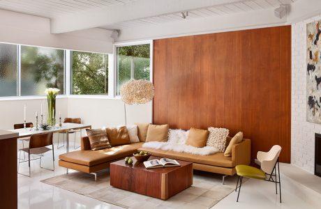 salon z narożną sofą na tle drewnianej ściany
