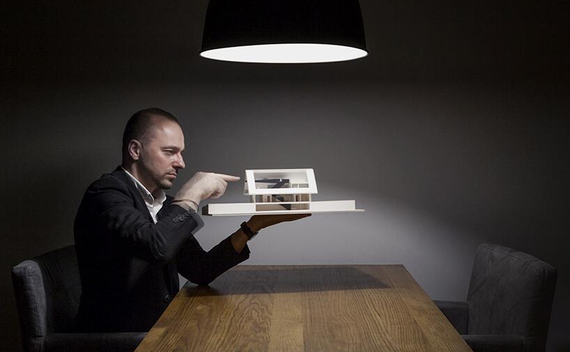 mężczyzna wgarniturze Bogusław Barnaś siedzący przy drewnianym stole zmodelem wdomu