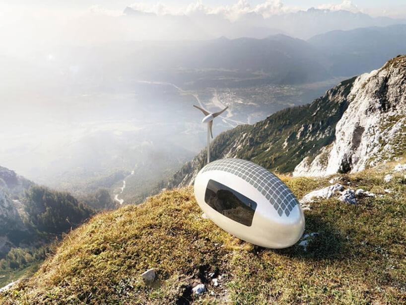 biała kapsuła zpanelami fotowoltaicznymi oraz małym ciemnym oknem na szczycie góry obok małego wiatraka