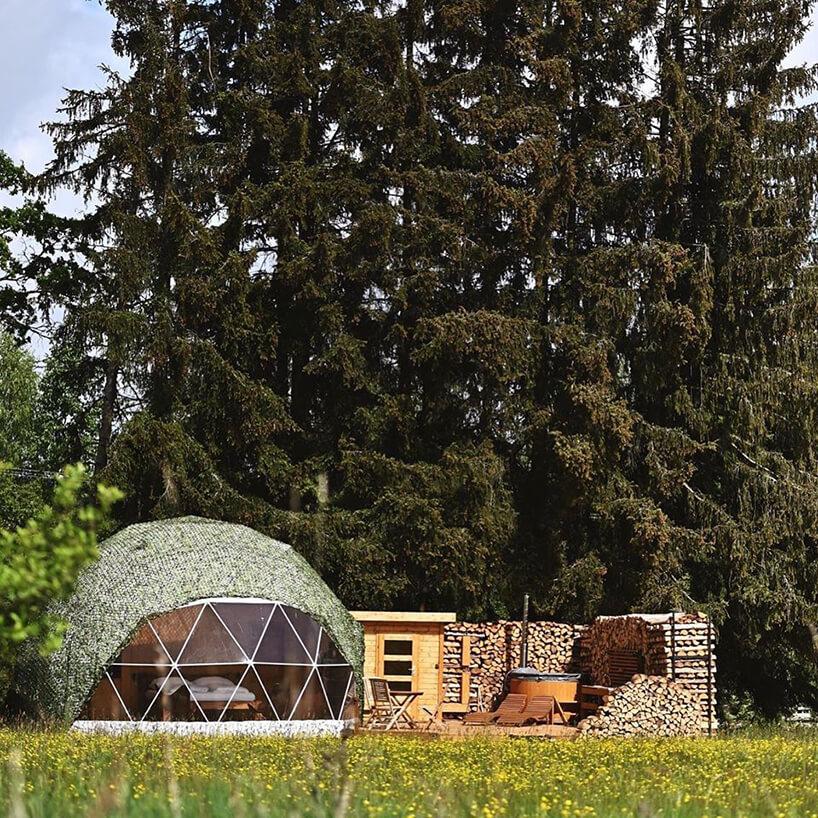 okrągłą kapsuła ztrójkątnymi konstrukcjami okiennymi na polanie