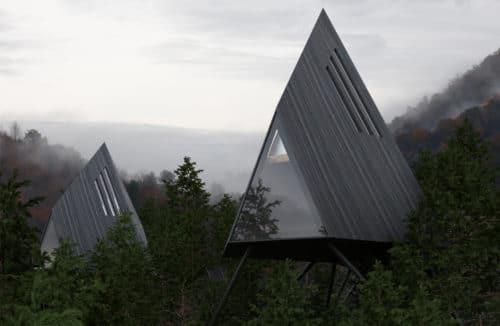 trójkątne z szarych desek domki w środku lasu