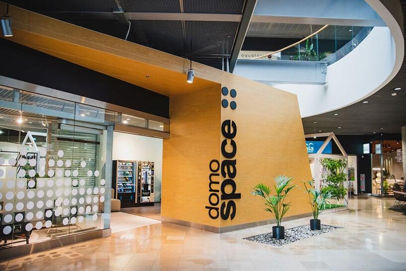 galeria handlowa zwejściem do sklepu zdużym elementem drewnianym oraz roślinami