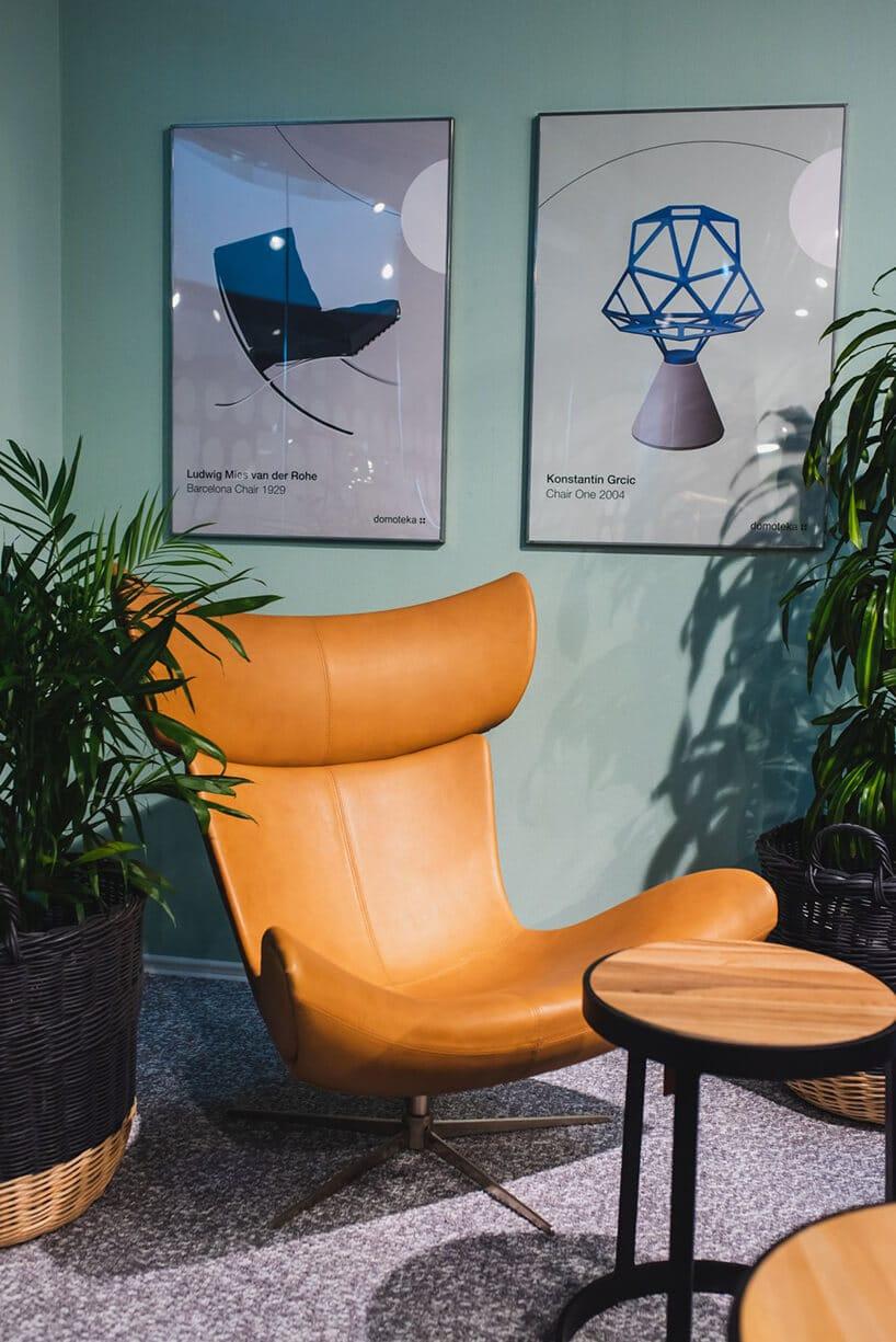 retro fotel zbrązową skórą oraz metalową podstawą na tle miętowej ściany przy drewnianym stoliczku