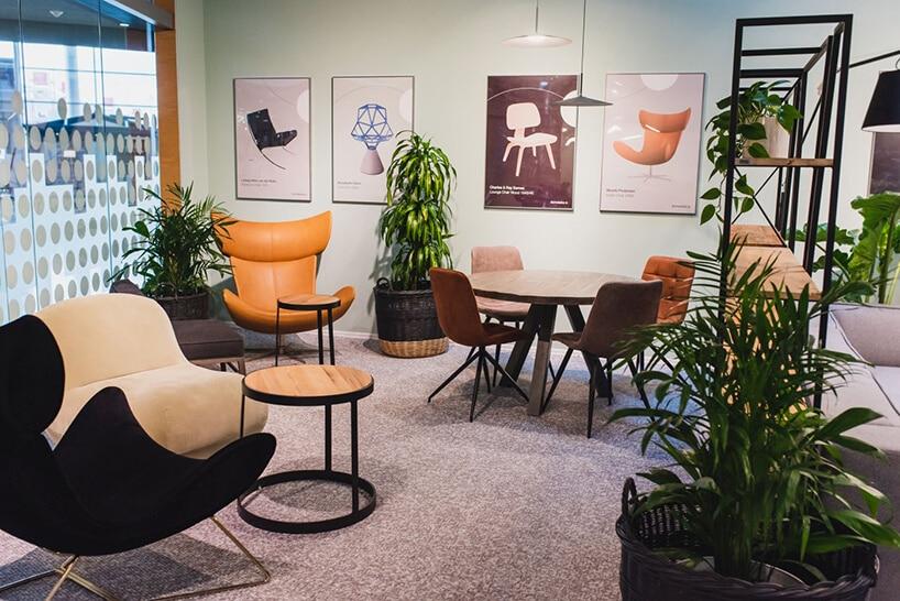 kilka foteli wmiętowym pomieszczeniu zwykładziną izielonymi roślinami