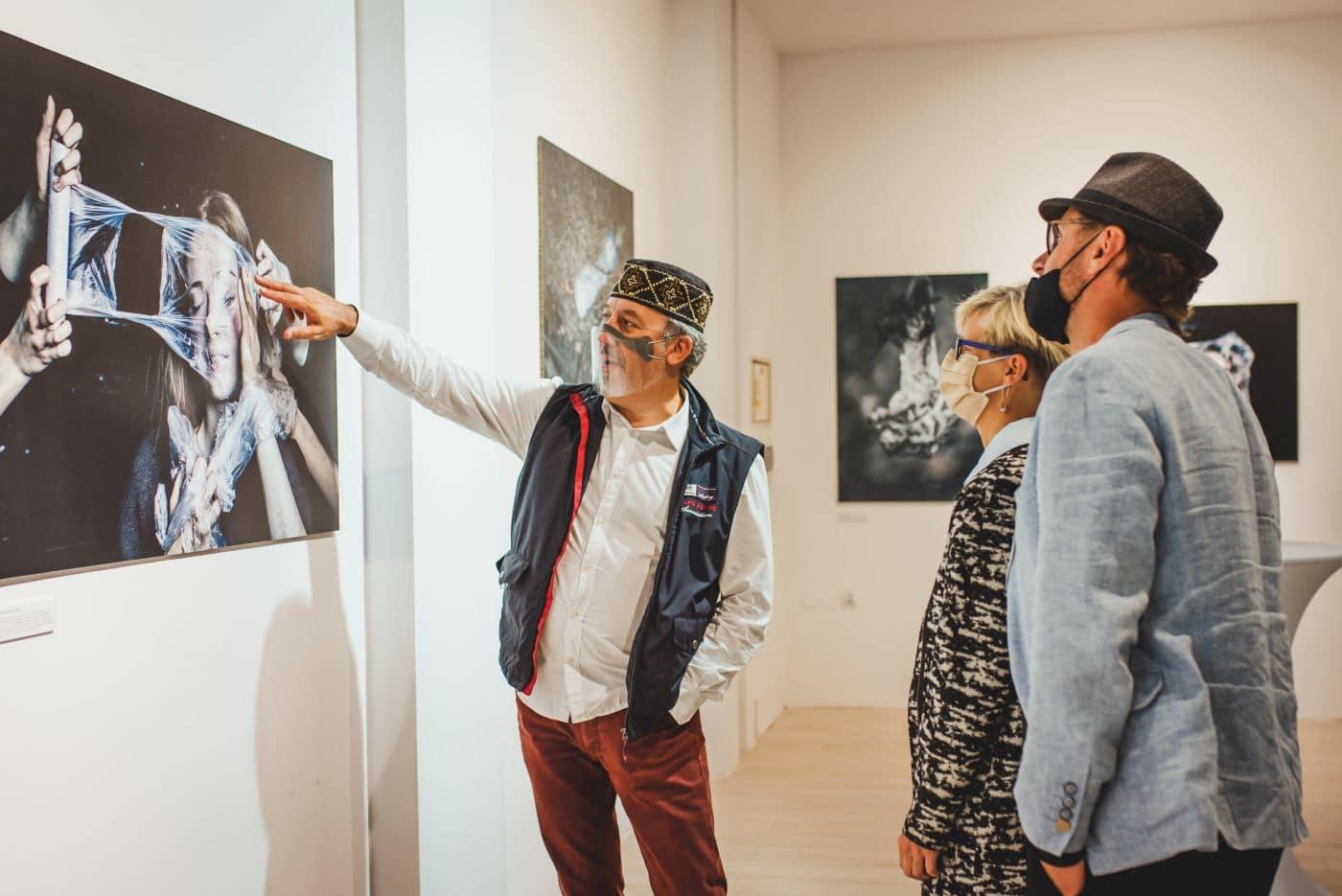 ludzie oglądający wystawę zdjęć wdomotece