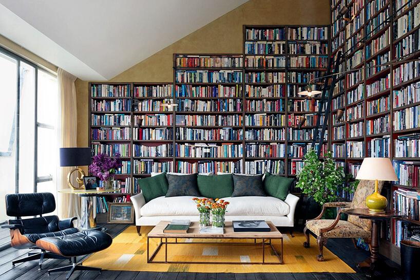 dwie ściany wsalonie zbiałą sofą jako domowa biblioteka pełna książek
