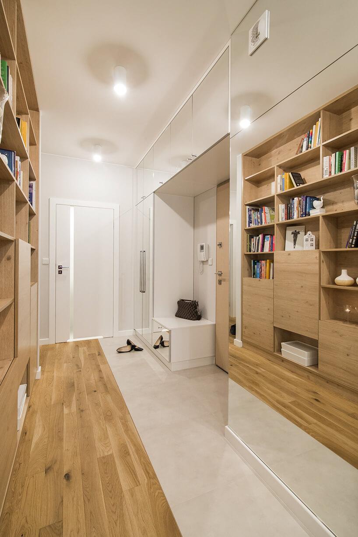 biały korytarz zdrewnianymi meblami jako domowa biblioteka zdrewnianymi półkami na książki