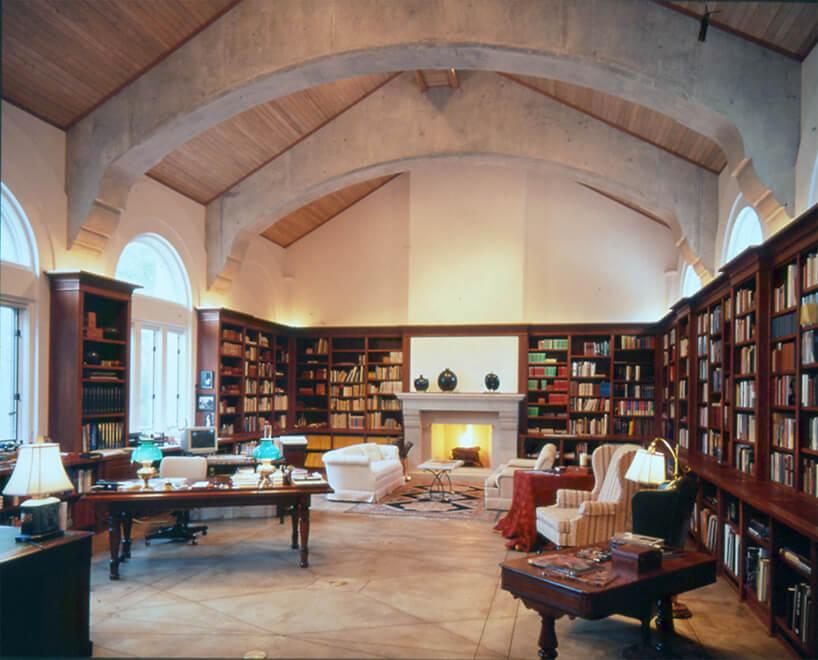 przestronny salon zbiałym kominkiem idomową biblioteką na ścianach dookoła
