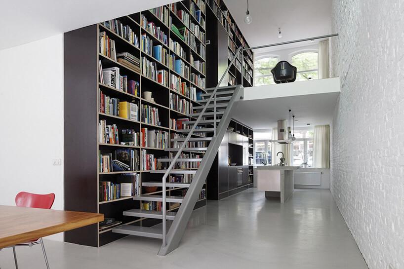 wysoka domowa biblioteka zszarymi metalowymi schodami na antresolę