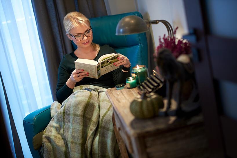 kobieta siedząca na niebieskim fotelu czytająca książkę