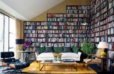 dwie ściany w salonie z białą sofą jako domowa biblioteka pełna książek
