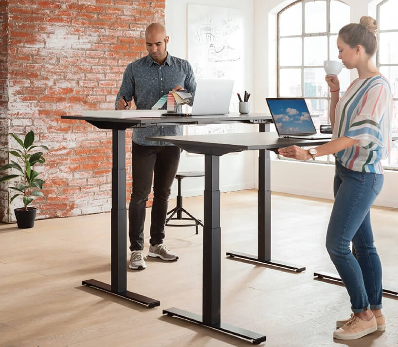 dwie osoby stojące wpokoju zczerwoną cegłą na ściana przy elektrycznie podnoszonych biurkach