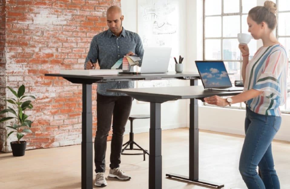 dwie osoby stojące w pokoju z czerwoną cegłą na ściana przy elektrycznie podnoszonych biurkach