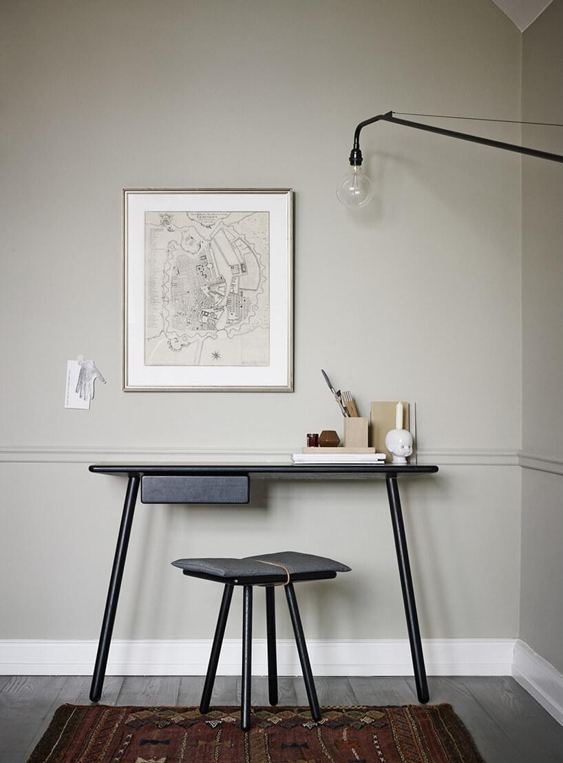 czarne nowoczesne biurko Georg od Skagerak zjedną małą szufladą iczarnym stołkiem na tle szarej ścianny