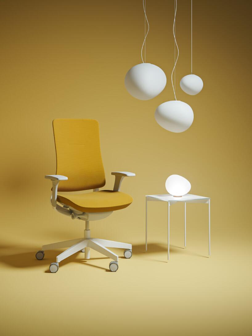 żółte krzesło Violle od Profim zbiałym stelażem ikółkami obok małego białego stolika zelegancką lampą