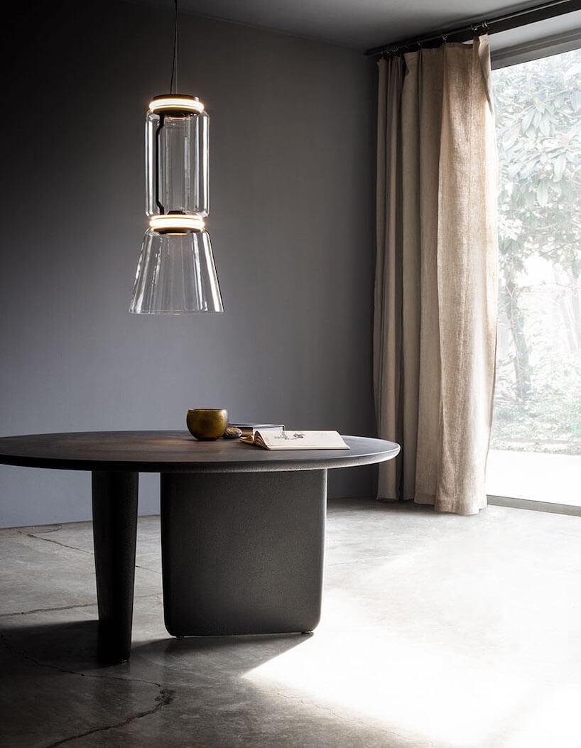 elegancka wisząca lampa Noctambule od Flos wdługim szklanym kloszu zdwoma świecącymi krążkami