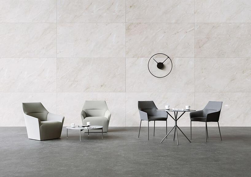 cztery fotele na tle kremowej kamiennej ściany