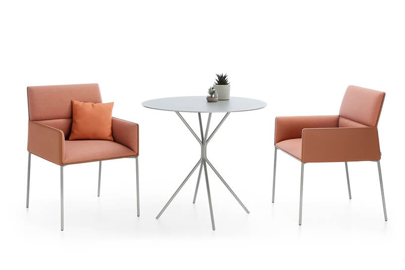 dwa łososiowe fotele przy małym stoliku