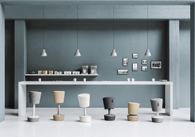 sześć różnokolorowych pufowych stołków na tle szarej ściany