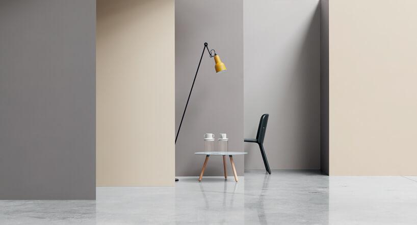 mały stolik zdrewnianymi nogami pod wysoką lampą stojącą zżółtym kloszem na podłodze kamiennej
