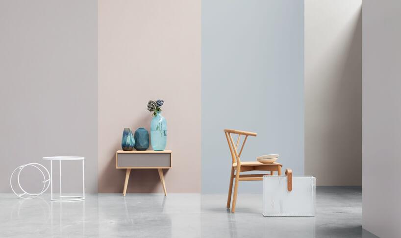 pastelowe ściany jako tło dla drewnianej szafki ztrzema wazonami drewnianego krzesła