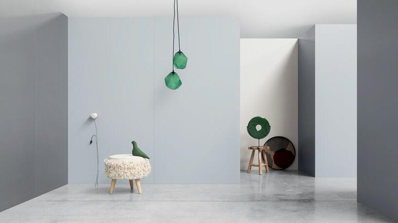 szare wnętrze zmałą pufą idwoma zielonymi lampami wiszącymi