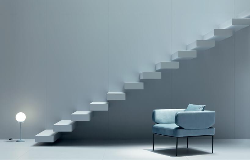 szare wnętrze ze schodami bez barierki iniebieski fotel zniskim oparciem
